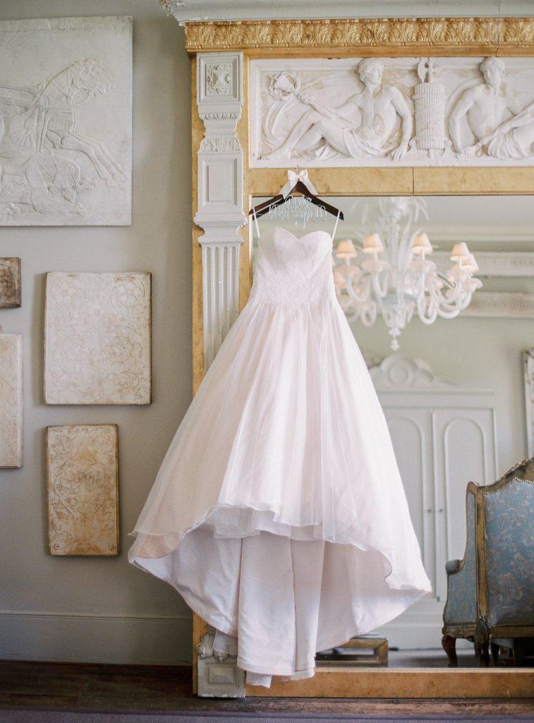 Blush pink wedding dress hanging on mirror