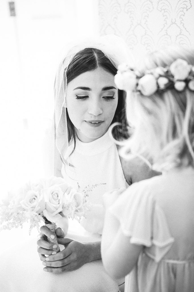 Bride speaking to flower girl