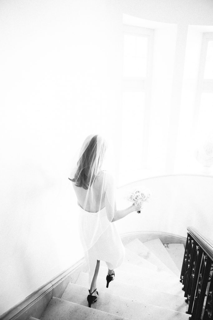 Bride walking down stairs black and white