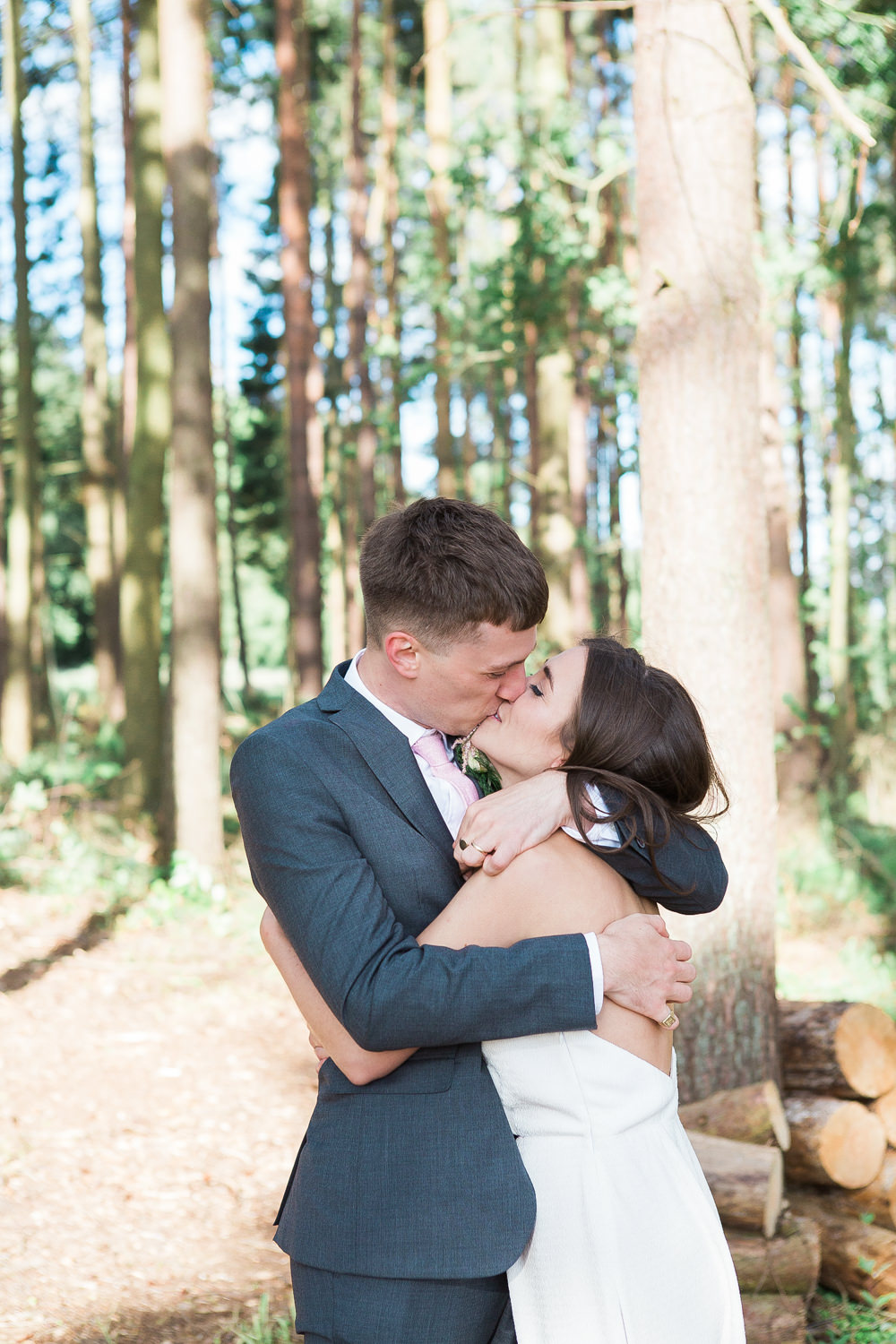 Bride and groom kiss in woodland