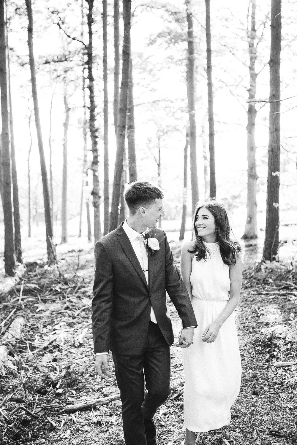 Bride and groom walk through woodland