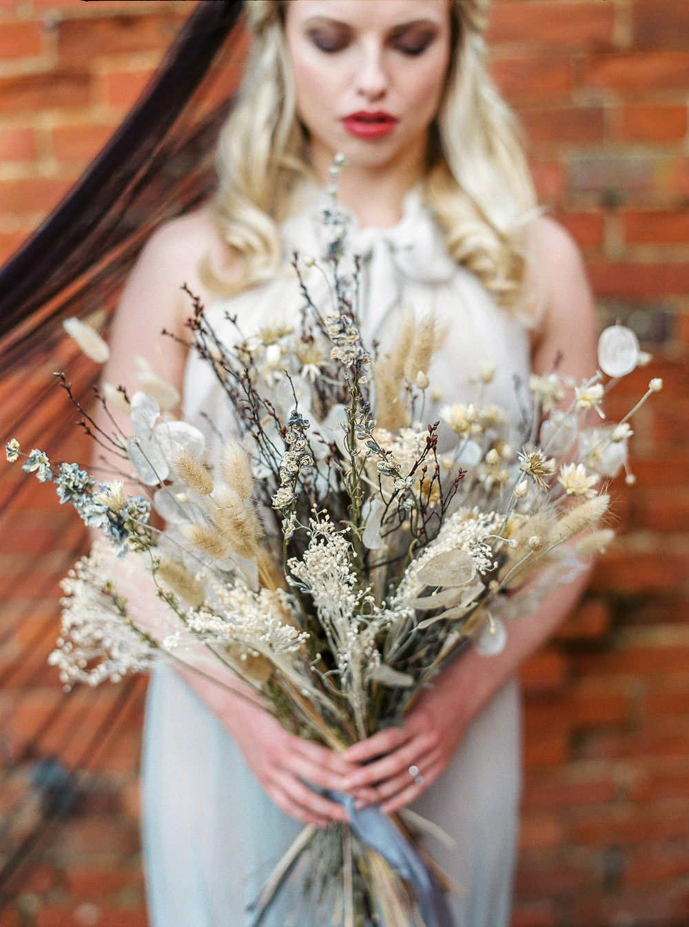 Bride wearing black veil, dried bouquet