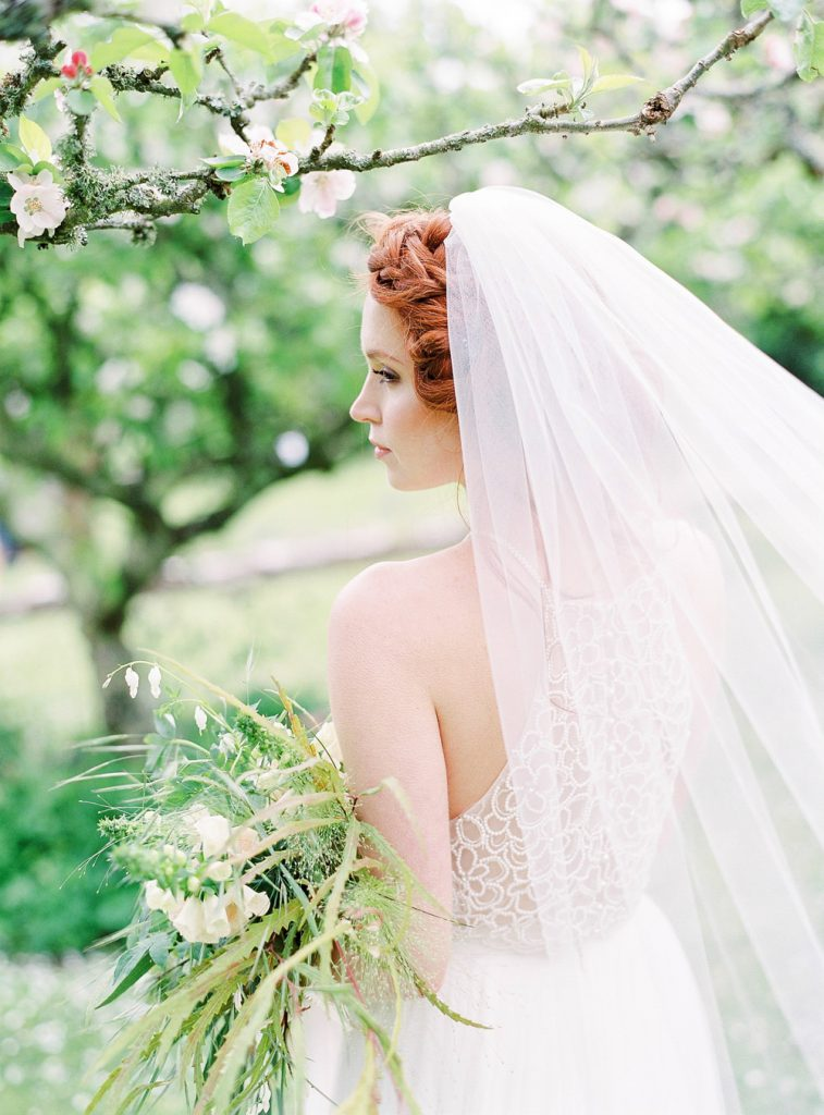 Red haired bride with veil and bouquet