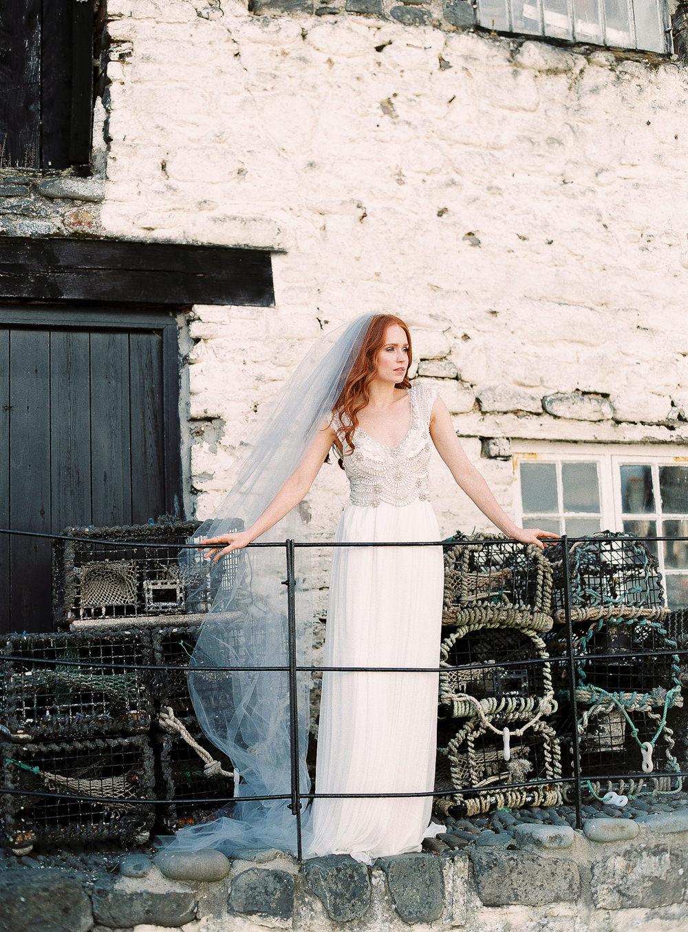 Bride with veil overlooking sea