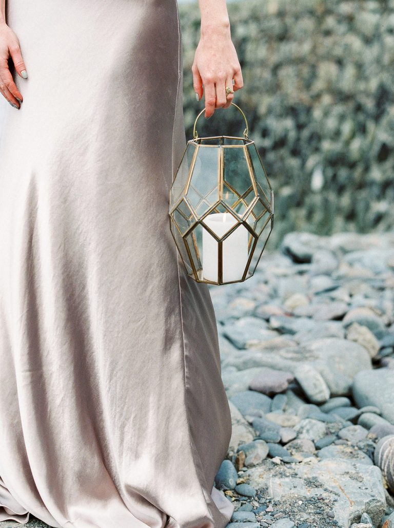 Gold hurricane lantern on beach