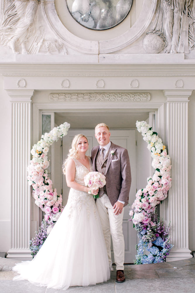 Bride and groom in Aynhoe Park orangery with ombre floral arch