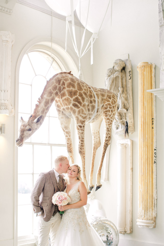 Bride and groom kissing under the giraffe at Aynhoe Park