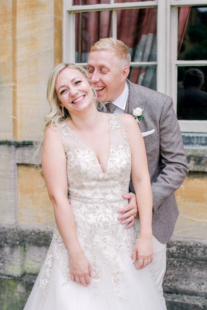 Bride and groom laughing outside Aynhoe Park