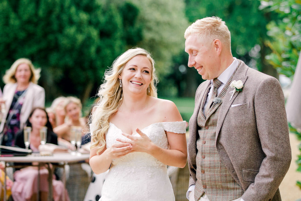 Bride and groom smiling during speeches
