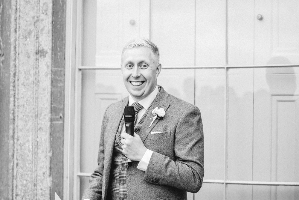 Groom smiling during speeches