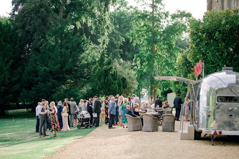 Wedding guests outside after the speeches at Aynhoe Park