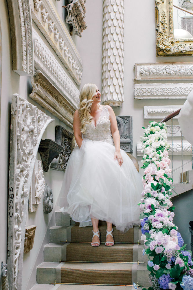 Bride walking down the stairs looking back to her bridesmaids
