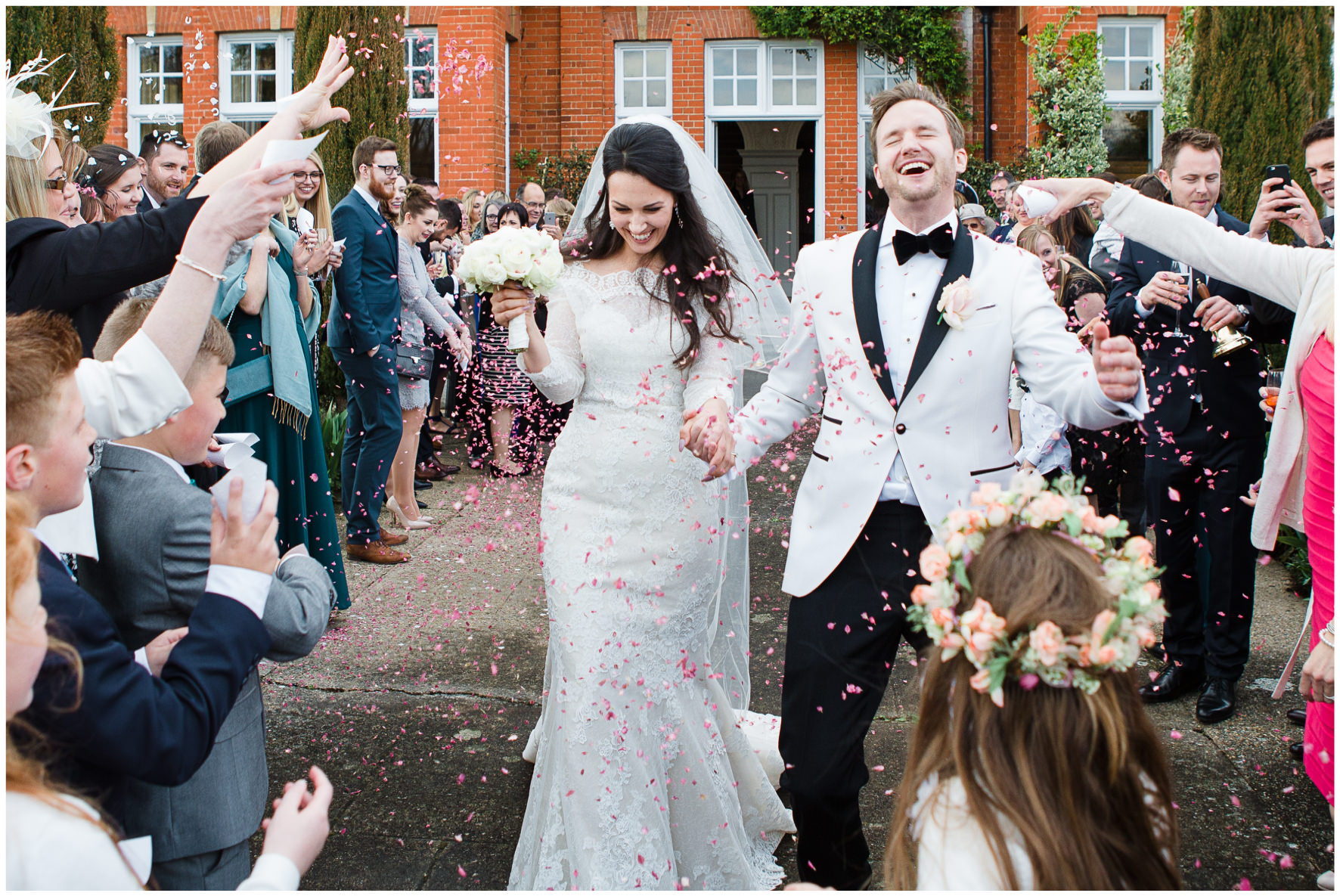 Lucy Davenport Photography, Katrina Otter Weddings, Chippenham Park, confetti, confetti tunnel, bride and groom