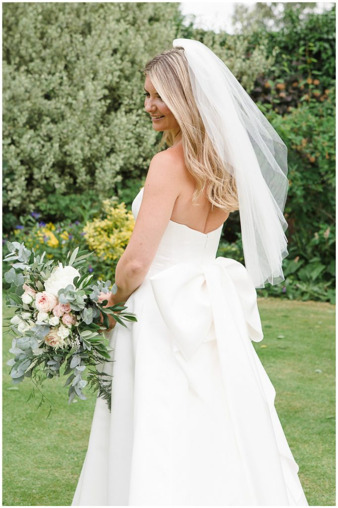 Bridal portrait, bride looking over her shoulder with bouquet and veil blowing in the wind.