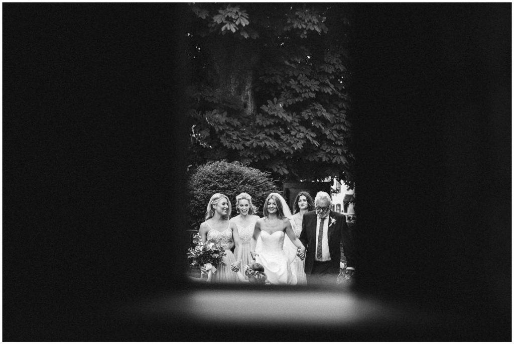Bride, father of the bride and bridesmaids walking down the church path.