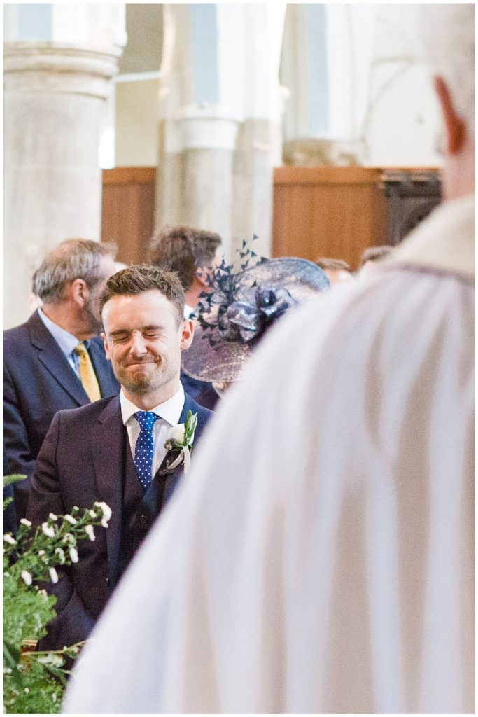 Groom holding back the emotions in church.