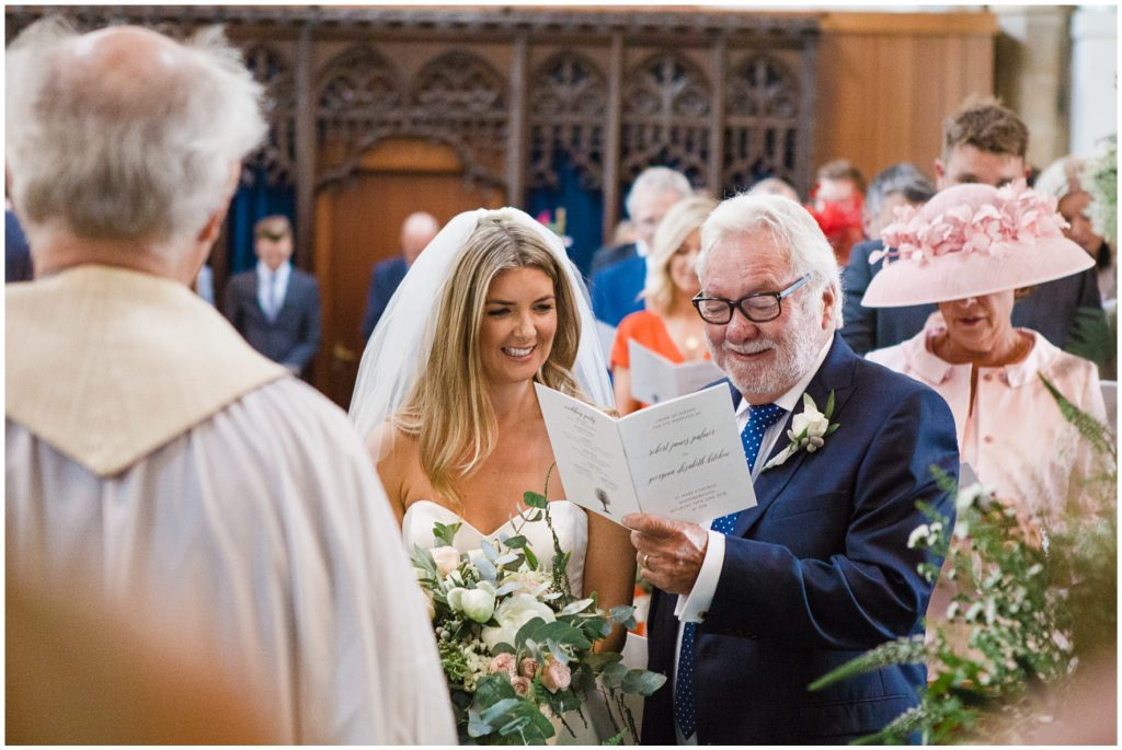 Bride and father of the bride looking at order of service.