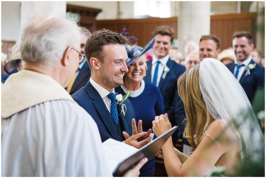 Groom laughing, putting his ring on as bride was struggling.