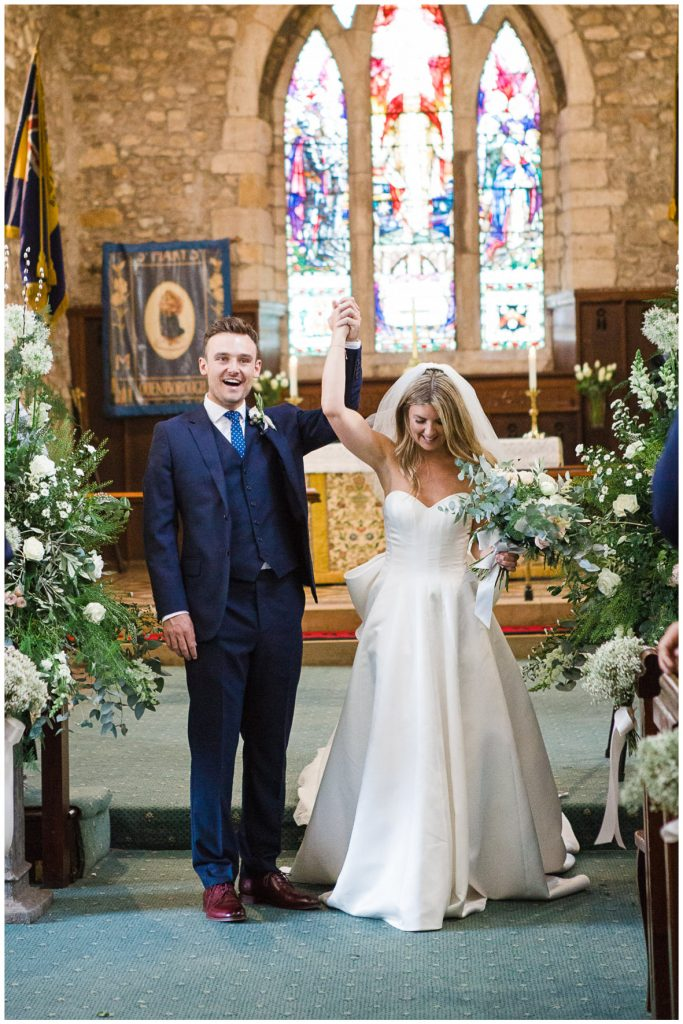 Bride and groom just married, arms in the air at the alter.