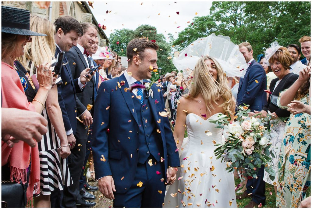 Bride and groom walking down a confetti tunnel.