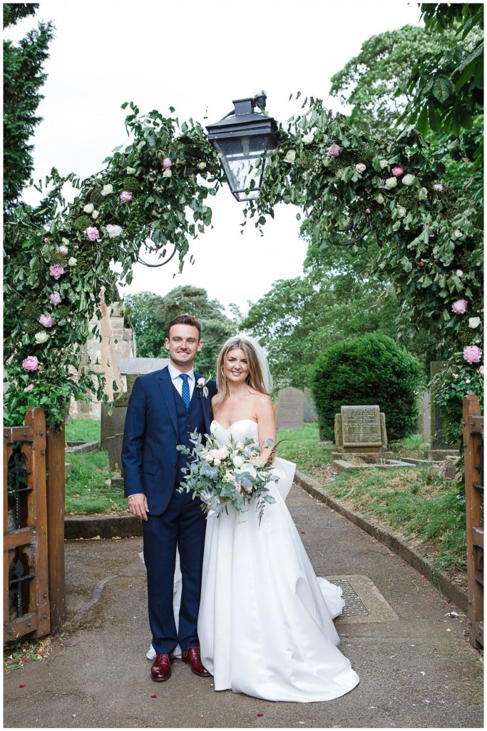 Bride and groom stood under the floral arch outside the church.