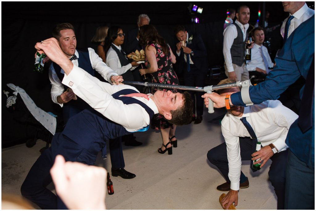 Wedding guests on the dance floor doing the limbo.