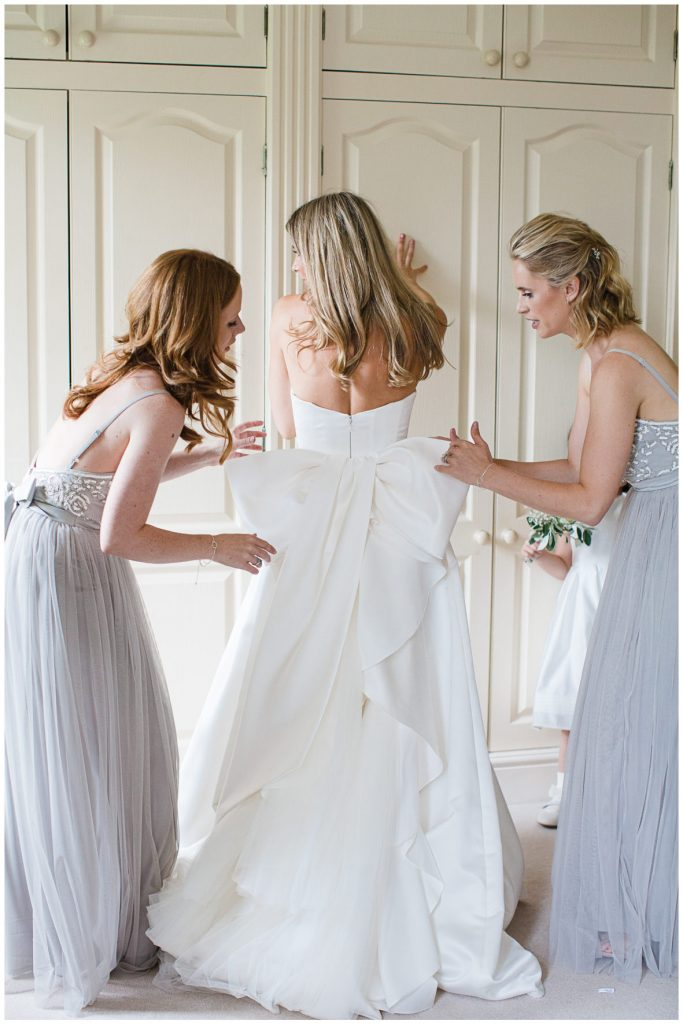 Bride wearing Badgley Mischa dress with bow detail. Bridesmaids helping bride to get ready.