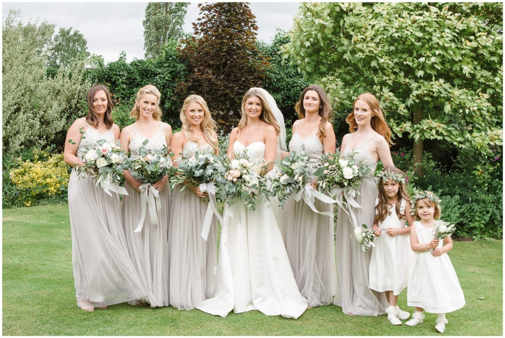 Bride and bridesmaids before the ceremony, all holding bouquets.