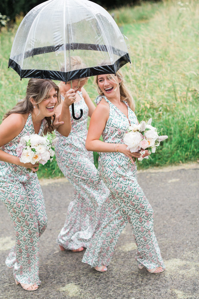 bridemaids arriving under an umbrella