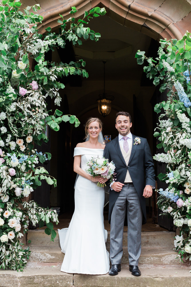 bride and groom outside church stood under floral arch