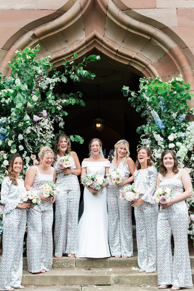 bride and bridesmaids under floral arch