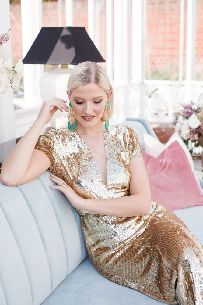 Bride wearing gold sequinned dress and green drop earrings