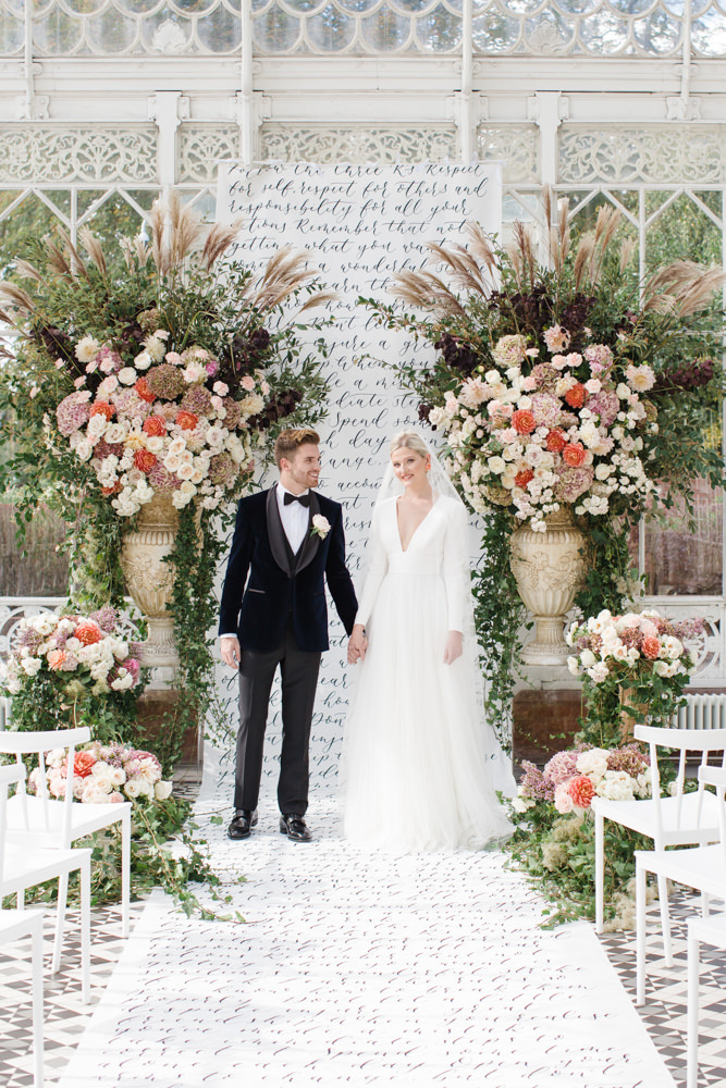 Bride and groom on calligraphy aisle and vast florals at Horniman Museum