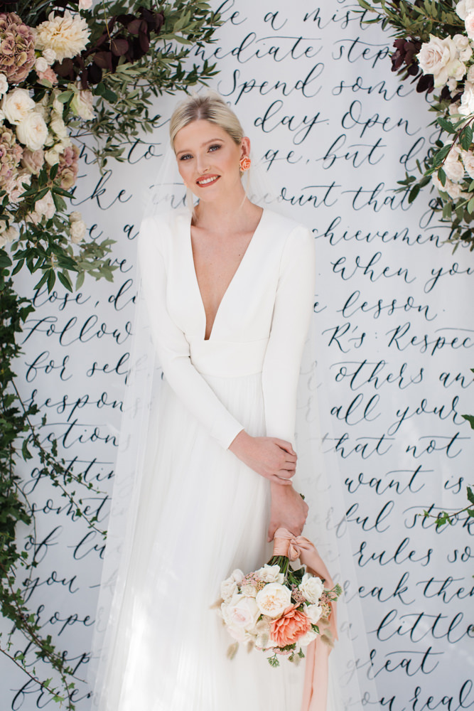 Bride holding bouquet in front of calligraphy backdrop