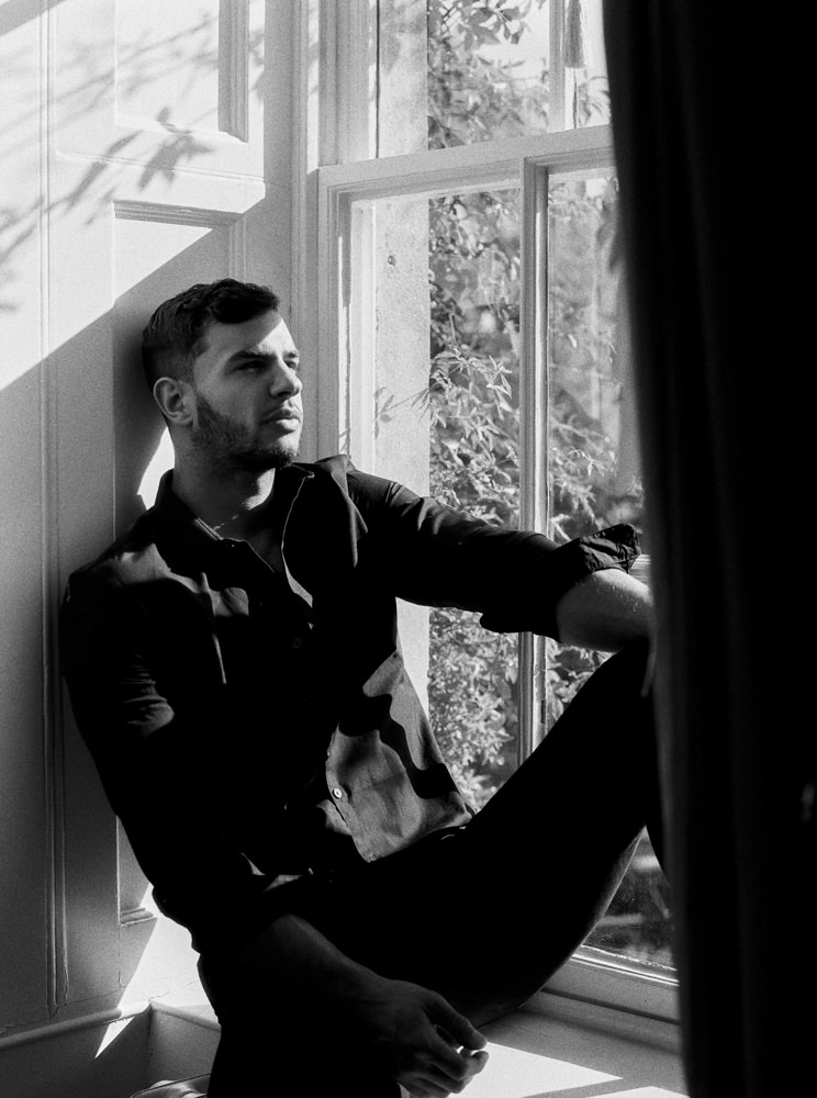 Groom sat on window sill at Cornwell Manor