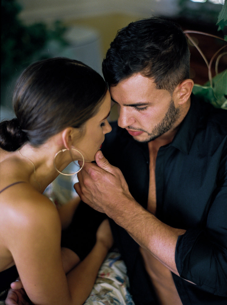 Close up of groom holding brides chin before kissing