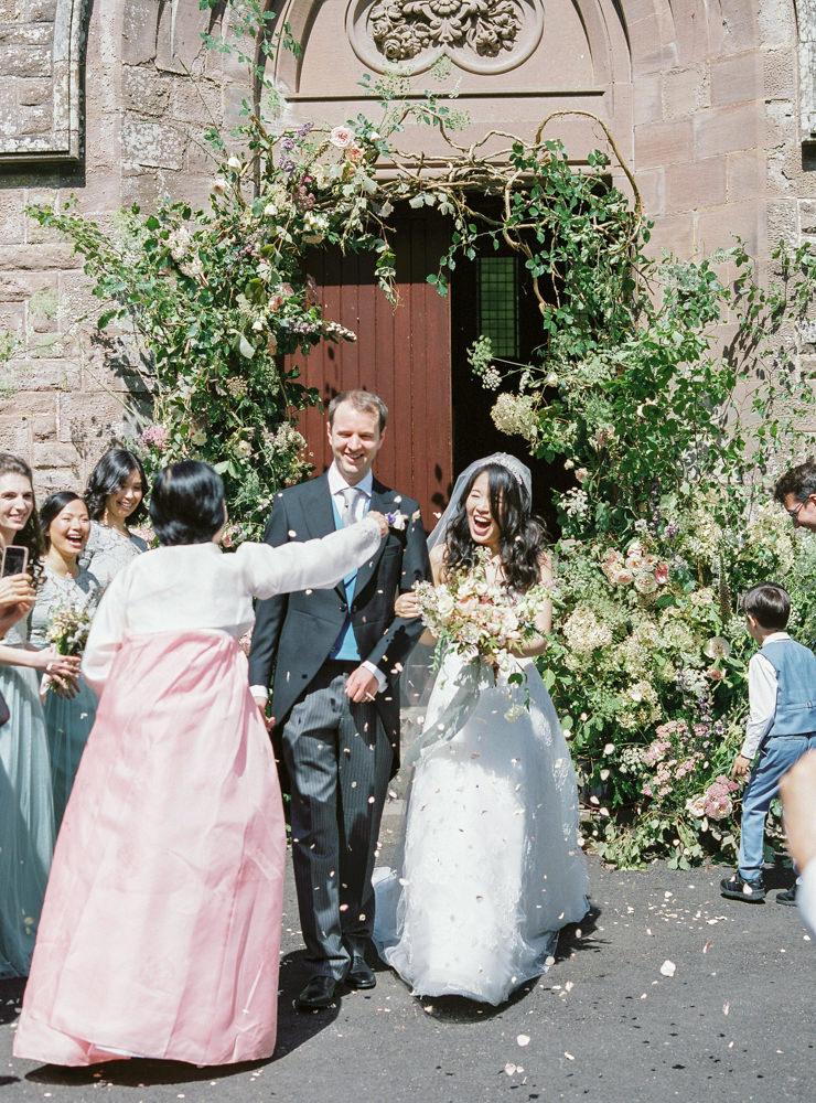 Bride and groom walk down confetti line