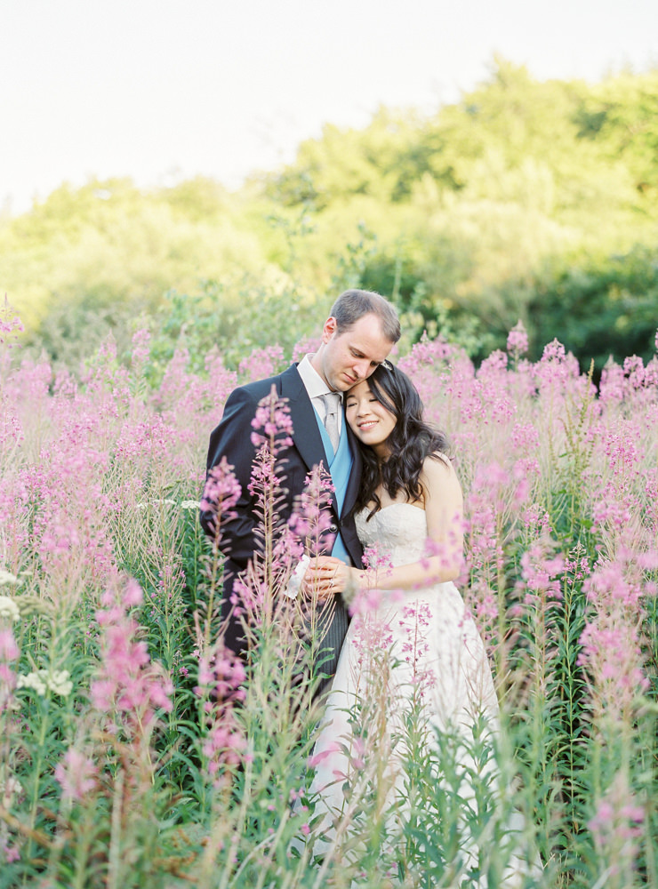 Bride and groom in field of pink