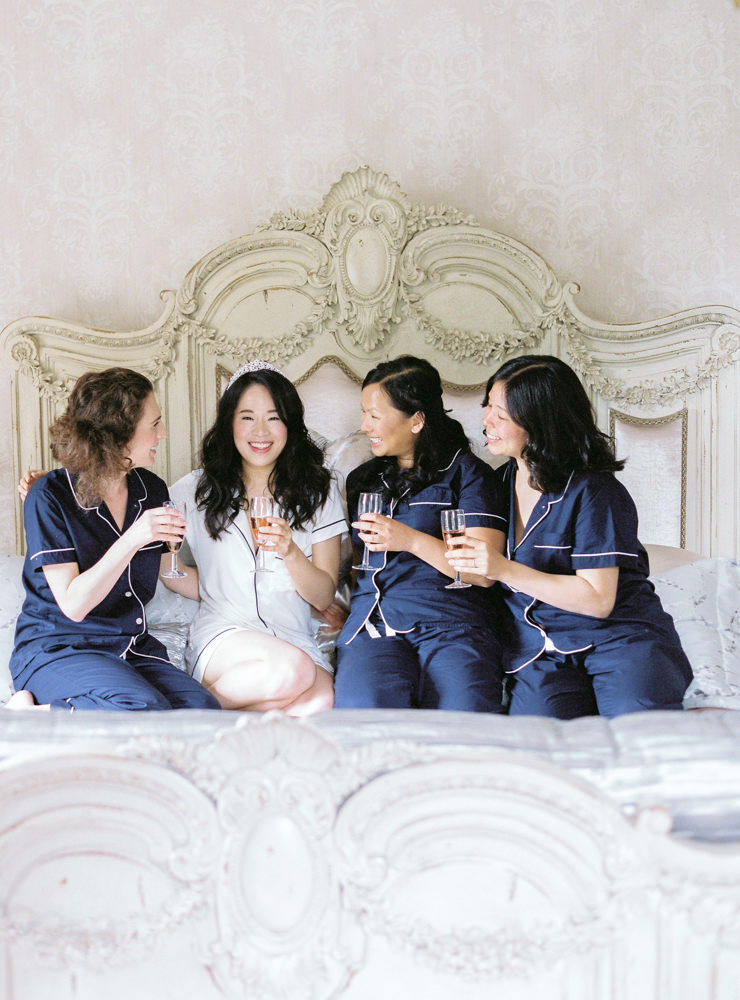 Bride and bridesmaids on bed with champagne