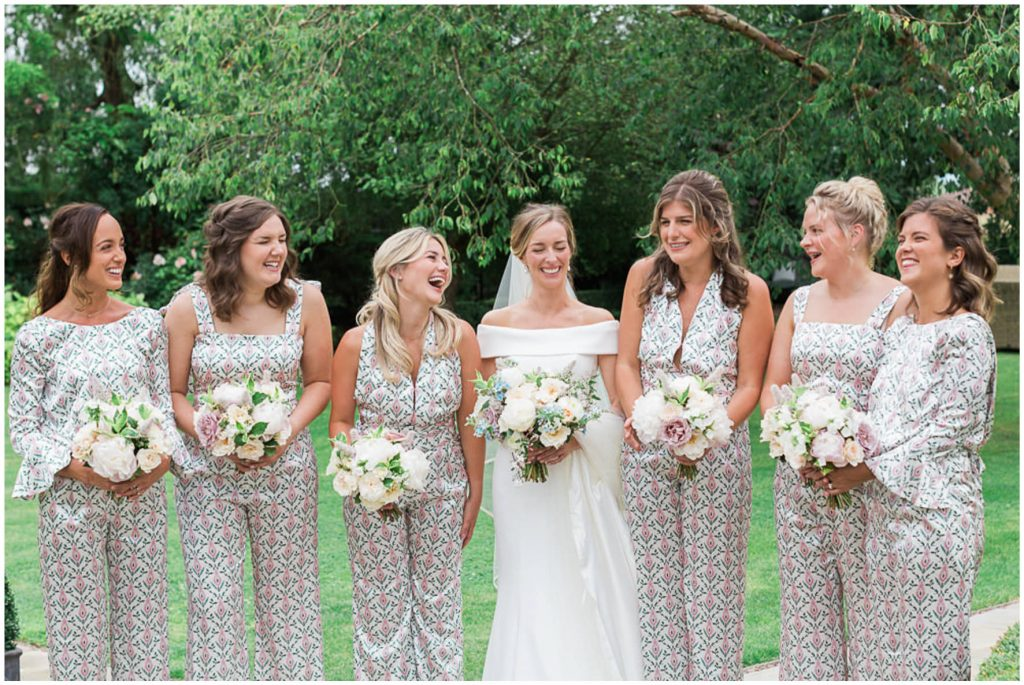 Bride wearing Suzanne Neville dress and bridesmaids laughing wearing Seren London.