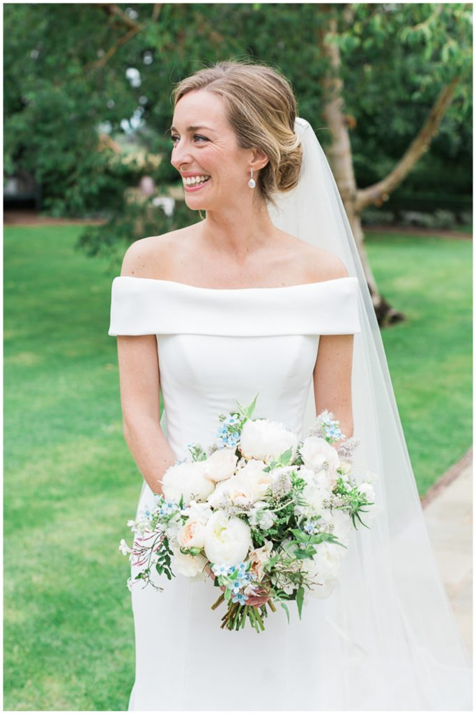 Bride wearing Suzanne Neville holding bouquet