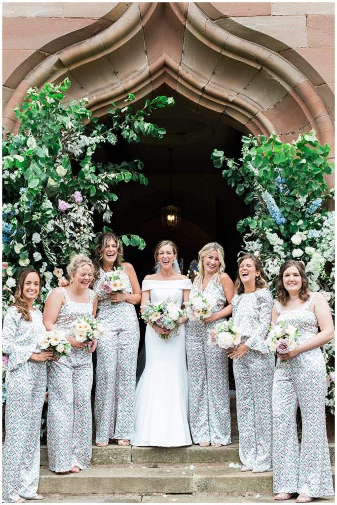 Bride and bridesmaids outside church with floral arch