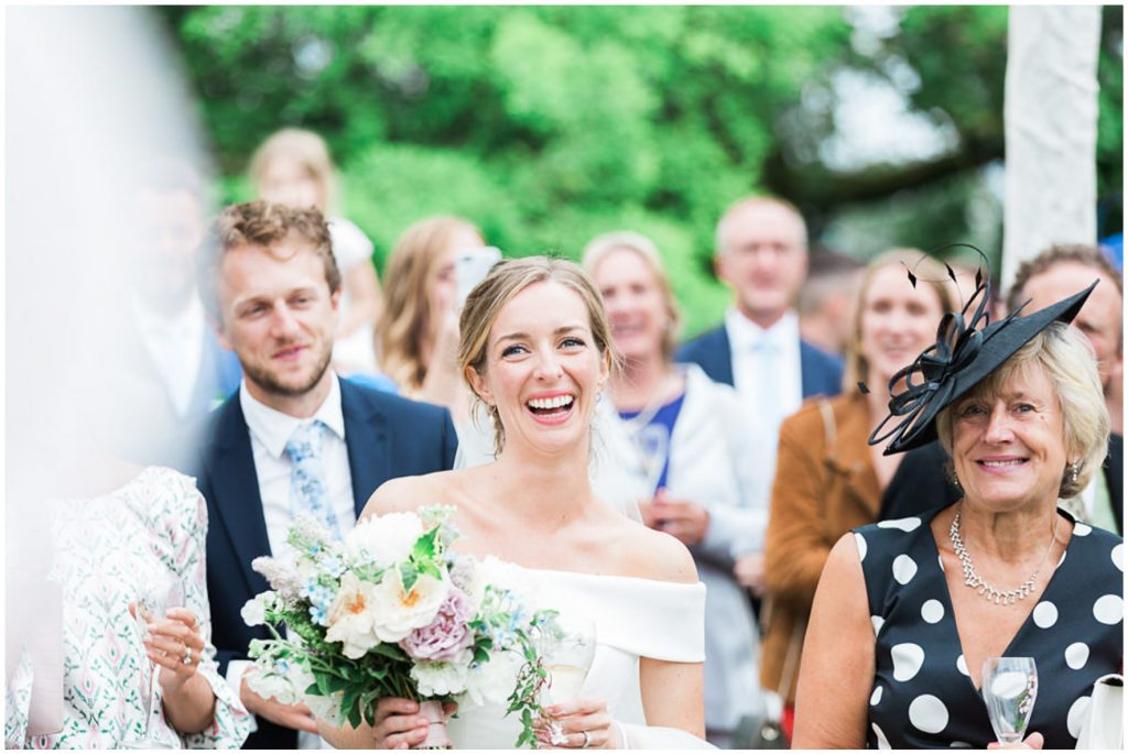 Bride laughing during outdoor speeches