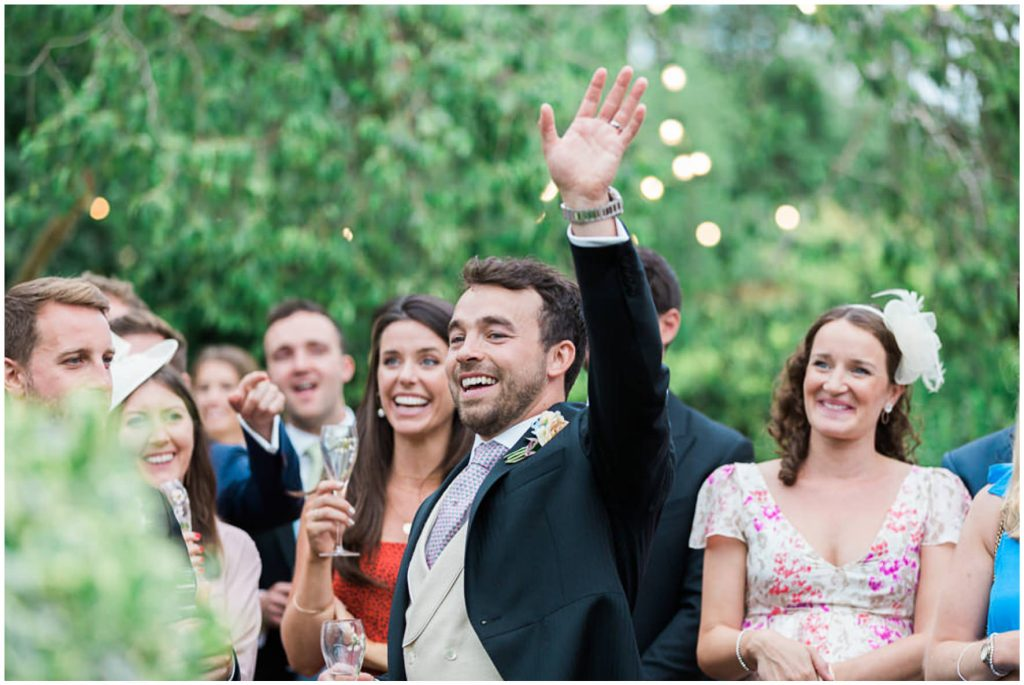 Groom waving and Wedding guests laughing during outdoor speeches