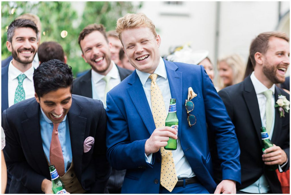 Wedding guests laughing during outdoor speeches