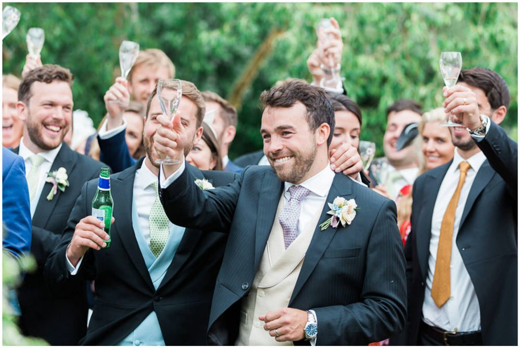 Groom and Wedding guests laughing cheering during outdoor speeches