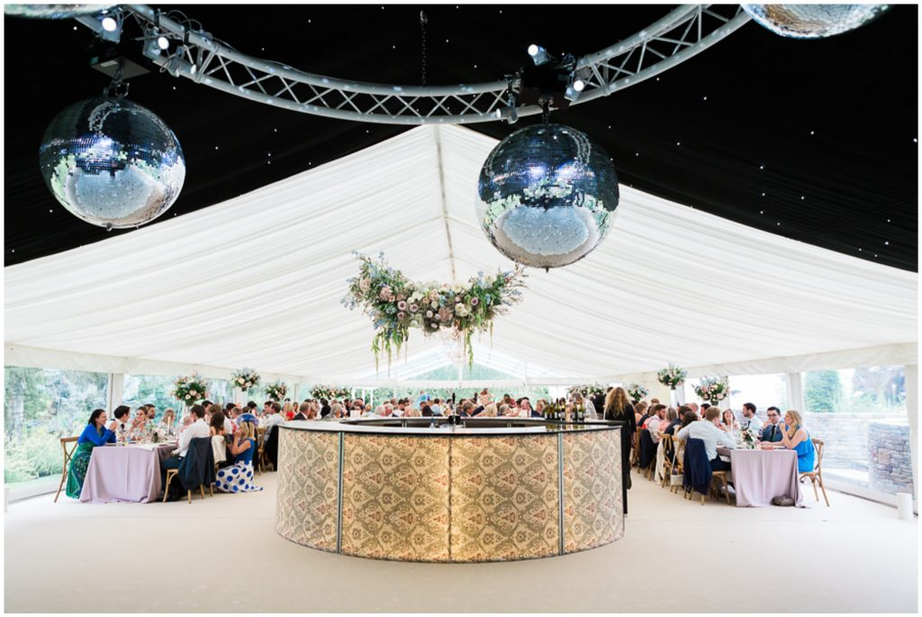 Good Intent marquee, wedding breakfast and personalised bar with hanging florals
