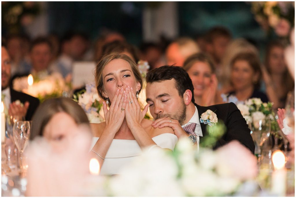 Groom kisses brides shoulder and bride blows a kiss during speeches