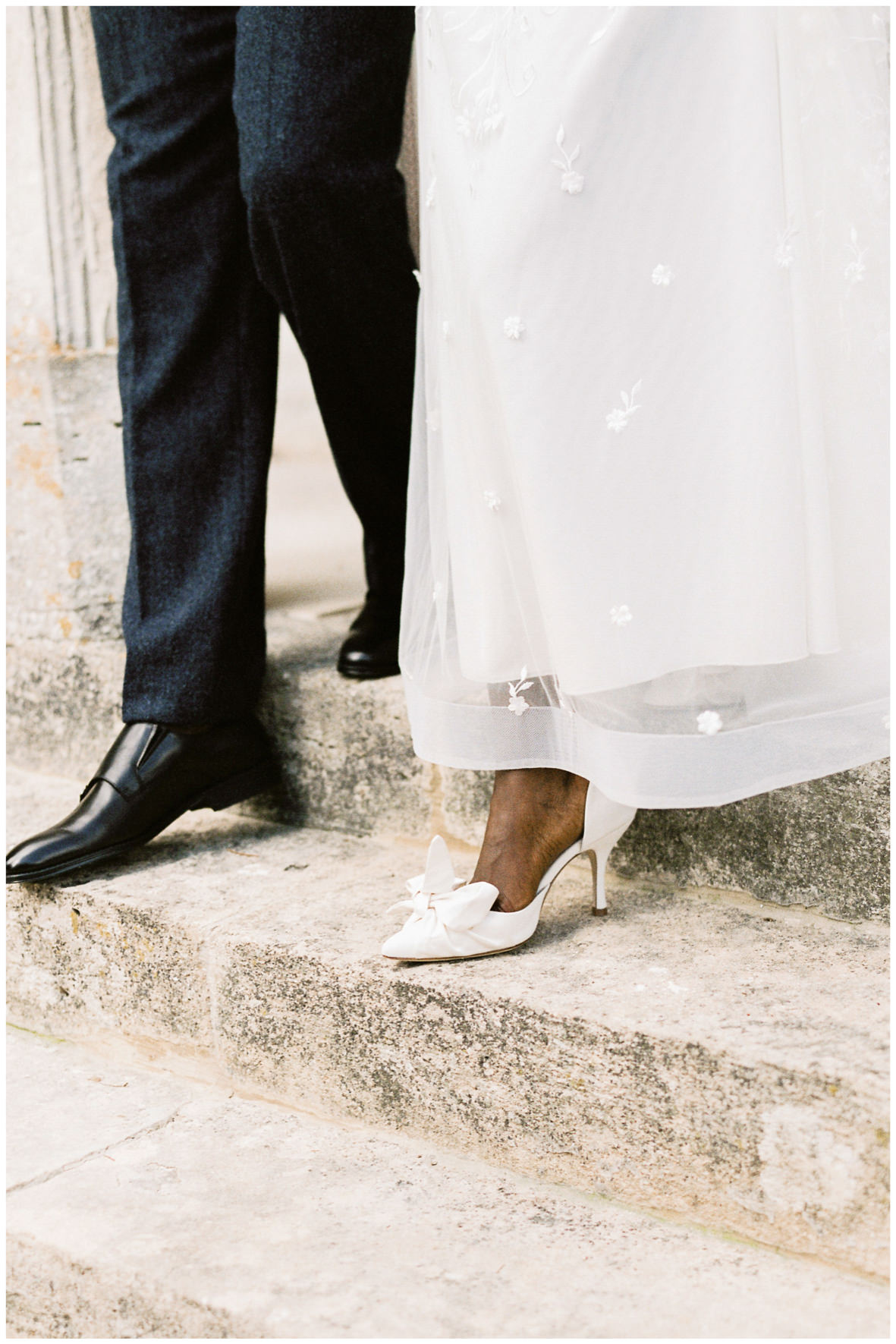 Bride and groom walking down steps at Barnsley House, bride wearing Emmy London shoes with bow