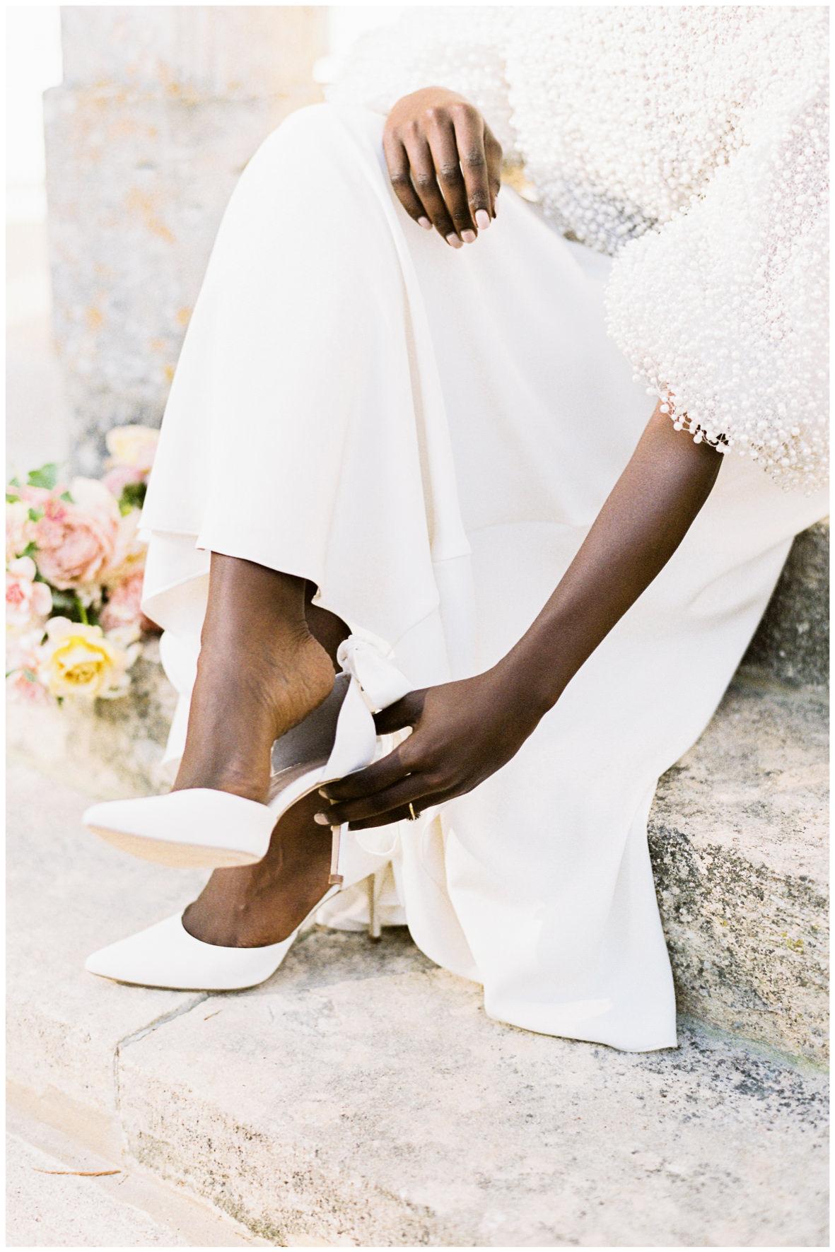 Bride wearing Romancera Madrid beaded wedding dress putting on Emmy London shoes.